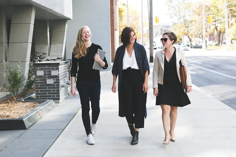 three business casual women walking to work and smiling