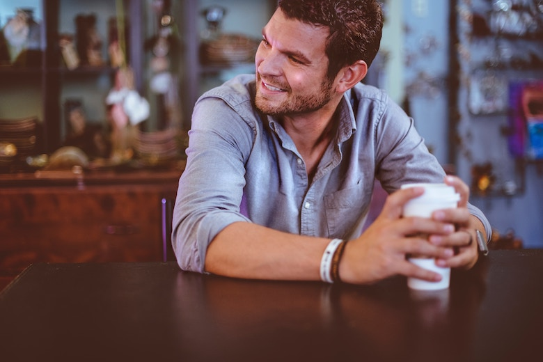 man with rolled sleeves drinking coffee at a table