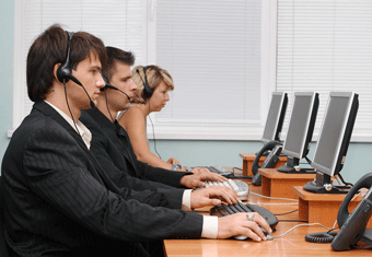 Two men and a woman wearing headsets work in a call center