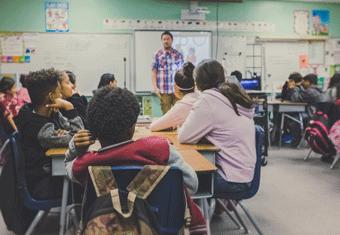 A teacher instructs a class of students using a digital whiteboard.
