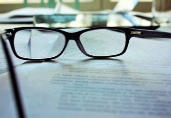 pair of glasses sitting on a newspaper talking about the 6 second resume challenge and its corresponding answers