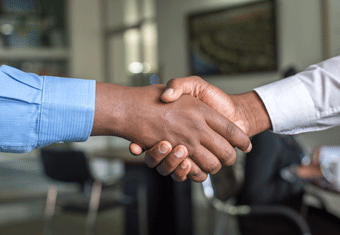An employer and new hire shake hands after agreeing on the salary requirements proposed in the applicant's cover letter.