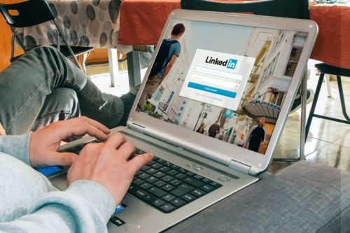 Man on laptop showing others how to add a resume to their LinkedIn account