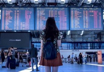 how to include study abroad on resume concept, airport photo of a young woman traveling to her study abroad destination